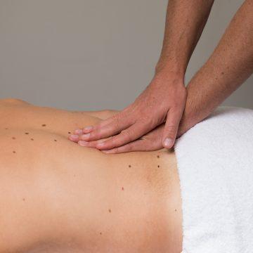 De osteopaat behandelt de rug met zijn handen