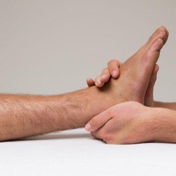 Osteopathie voor sporters. De osteopaat onderzoekt de enkel.